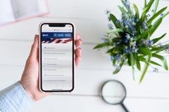 KHARKIV, UKRAINE - 10 avril 2019 : La femme tient l'iPhone X d'Apple avec l'IRS site de gouvernement sur l'?cran images libres de droits