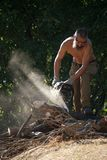 Barefoot man with a beard cuts firewood for the fire by chainsaw in the morning sun. Kharkiv, Ukraine - July 05, 2019: Barefoot man with a beard cuts firewood stock photography