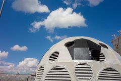 Kharkiv, Ukraine, July, 2019 Football ball installation near sport complex and stadium. City landscape in summer day. Decorated. Ventilating tower of modern royalty free stock photography