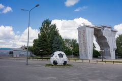 Kharkiv, Ukraine, July, 2019 Football ball installation and outside climbing wall near sport complex and stadium. City landscape. In summer day. Decorated royalty free stock photography