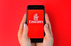 KHARKIV, UKRAINE - JULY 10, 2019: Illustrative editorial of Emirates airlines logo on smartphone screen. In female hands royalty free stock photos