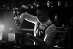 KHARKOV, DE OEKRA?NE - APRIL 26, 2019: De barman bereidt een cocktail bij de bar voor stock foto