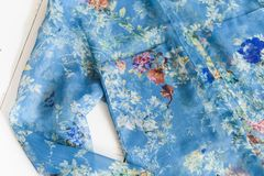 KHARKOV, UCRÂNIA - 27 DE ABRIL DE 2019: Detalhes de blusa floral azul Veste o conceito Fundo de madeira foto de stock royalty free