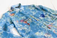 KHARKOV, UCRÂNIA - 27 DE ABRIL DE 2019: Detalhes de blusa floral azul Veste o conceito Fundo de madeira fotos de stock royalty free