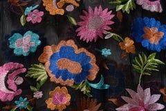 KHARKOV, UCRÂNIA - 27 DE ABRIL DE 2019: Flores brilhantes bordadas na tela preta Close-up fotografia de stock