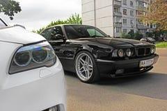 Kharkov, Ucraina Autunno, settembre 2017; BMW combinato Due BMW M5 - in bianco e nero BMW M5 F10 e M5 E34 nella città fotografia stock libera da diritti