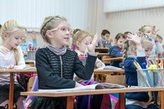 Kharkov, Ucrania - 30 de noviembre de 2017: Los niños aumentan sus manos que se sientan en el escritorio Fotos de archivo libres de regalías