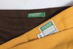 KHARKOV UKRAINA - JANUARI 17, 2019: Etiketten med ord förenade färger av benetton på gula och bruna kjolar Kläder och tillbehör arkivbilder