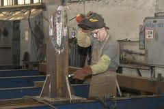KHARKOV UKRAINA - 8 JUNI 2017: Metalworking shoppar arbetare arbetar bak maskiner och apparaturar för att skapa stålstrukturer kh Royaltyfria Foton