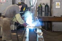 KHARKOV UKRAINA - 8 JUNI 2017: Metalworking shoppar arbetare arbetar bak maskiner och apparaturar för att skapa stålstrukturer kh Arkivbild