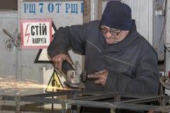 KHARKOV UKRAINA - 8 JUNI 2017: Metalworking shoppar arbetare arbetar bak maskiner och apparaturar för att skapa stålstrukturer kh Royaltyfria Bilder
