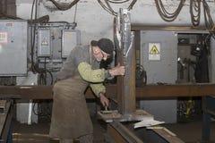KHARKOV UKRAINA - 8 JUNI 2017: Metalworking shoppar arbetare arbetar bak maskiner och apparaturar för att skapa stålstrukturer kh Royaltyfri Foto