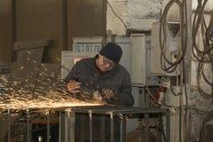 KHARKOV UKRAINA - 8 JUNI 2017: Metalworking shoppar arbetare arbetar bak maskiner och apparaturar för att skapa stålstrukturer kh Arkivfoto