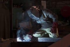 KHARKOV UKRAINA - 8 JUNI 2017: Metalworking shoppar arbetare arbetar bak maskiner och apparaturar för att skapa stålstrukturer kh Royaltyfri Bild