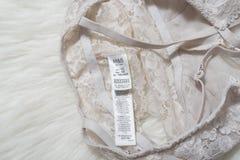 KHARKOV UKRAINA, STYCZEŃ, - 17, 2019: Etykietka na nagich postaci menchiach zasznurowywa stanika na białym futerku Odziewa i akce obrazy stock