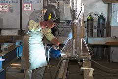 Metalworking shop workers work behind machines and apparatuses to create steel structures Royalty Free Stock Images