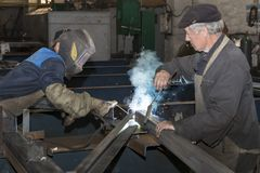 Metalworking shop workers work behind machines and apparatuses to create steel structures Royalty Free Stock Photos