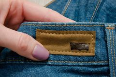 KHARKOV, UKRAINE - 02 MARCH 2018: Lather label Levis on jeans in. Female hand Royalty Free Stock Images