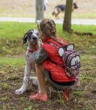 Kherson, de OEKRAÏNE - September 15, 2018: meisje in een rood vest met een rugzak die een puppy witte marmeren Duitse hond strijk stock afbeelding