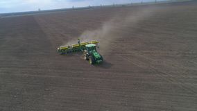 Aerial shot of farmer in modern tractor is working on dry field during plowing at spring season stock video