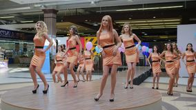 Beauty contest, nice young contestants with long hair in a dress on high heeled posing for the camera on catwalk