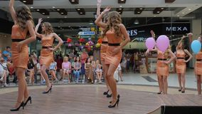 Girls with long hair in dress on high heels dancing for camera and jury on stage at beauty contest