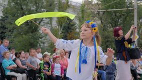 Kid with bright ribbon in hands dances in square, child in national costume with maschette ribbon in open air, stock video