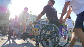 Men invalid on wheel chair pulls cable of training apparatus with trainer in sunshine. Kherson, Ukraine 24 August 2017: men invalid on wheel chair pulls cable of stock video footage