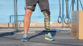 Strong arms of male handicapped with prosthetic leg in form of sport raises heavy weight