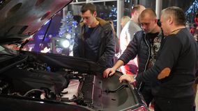 Car sales center, men with interest are considering new vehicle with an open bonnet. Kherson, Ukraine 22 December 2017: car sales center, men with interest are stock video