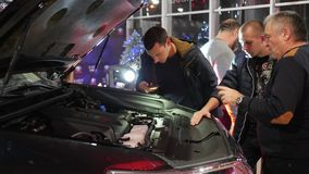 Company of male with interest are considering new automobile with an open hood in car sales center. Kherson, Ukraine 22 December 2017: company of male with stock footage