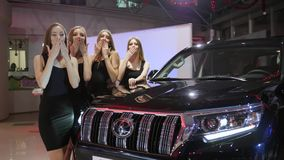 Group of beautiful female send an air kiss and wave hands at car in motor show. Kherson, Ukraine 22 December 2017: group of beautiful female send an air kiss and stock footage