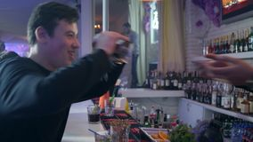 Guy takes from bartender two glasses and have fun with your friends near bar counter at weekend. Kherson, Ukraine, 11 December 2017: guy takes from bartender two stock video footage