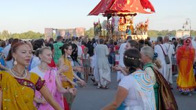 Crowd of joyful people dancing near colorful cart outdoors, holiday krishna, women in vivid indian costumes dance stock video
