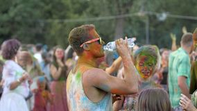Holi festival atmosphere, guy with glasses and bright powder drink water in crowd outdoors, young people enjoying colors stock footage