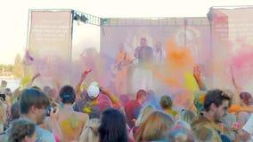 Worship Krishna, open air festival, followers hare krishna sing mantra, people in colored powder enjoying music stock footage