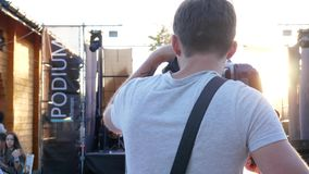 Videographer with camera is getting ready to work at famous event on open air stock video