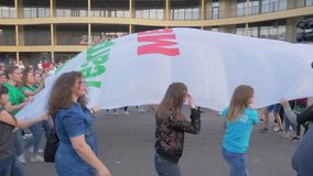 Crowd of young people waving large canvas during street parade in city. KHERSON, UKRAINE - MAY 20, 2019: Festival Melpomene of Tavria, crowd of young people stock video footage