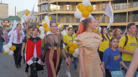 Festivities, crowd youth in different costumes with balloons walk along city street and shout chants on open air. KHERSON, UKRAINE - MAY 20, 2019: Festival stock video footage