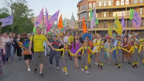 Happy crowd of people of different ages in bright costumes with colored flags walking down city street during festival. Kherson, Ukraine - May 20, 2019: Festival stock video footage