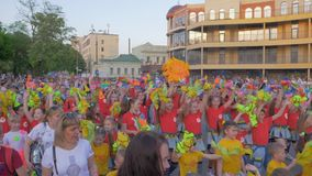Holiday summer festival, many children and teenagers in bright clothes waving hands and shouting chants on city street. KHERSON, UKRAINE - MAY 20, 2019: Festival stock footage