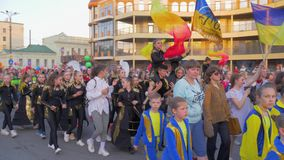 National parade, crowd youth in different costumes with Ukrainian flags walk along city street and shout chants on open. Kherson, Ukraine - May 20, 2019 stock video footage