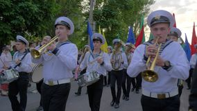 Sailors play musical instruments and carry colored flags on the street during the parade stock footage