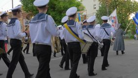 Sailors in uniform play on musical instruments during the march on parade and carry different flags at the street stock video footage