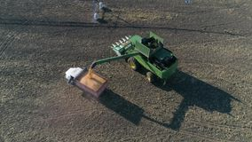 Agribusiness, Combine harvester pouring corn in truck on field for transportation in aerial view stock footage