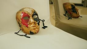 Art exhibition of vivid masks for masquerade close-up on white armchair in museum. Kherson, Ukraine 20 October 2017: art exhibition of vivid masks for masquerade stock video footage