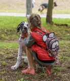 Kherson, UKRAINE - September 15, 2018: little girl in a red vest with a backpack stroking a puppy white marble German dog. Day stock image