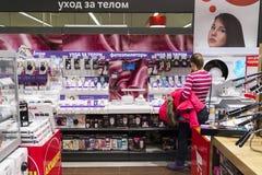 Khimki,俄罗斯- 2015年12月22日 妇女选择在卖电子和家用电器的Mvideo大连锁店的epilator 库存照片