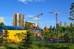 Khimki, Rusia - 30 de mayo 2017 Complejo del juego de niños en fondo de la construcción inferior en la orilla de Eco del parque Imagenes de archivo