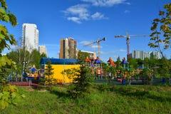 Khimki, Rusia - 30 de mayo 2017 Complejo del juego de niños en fondo de la construcción inferior en la orilla de Eco del parque Imágenes de archivo libres de regalías